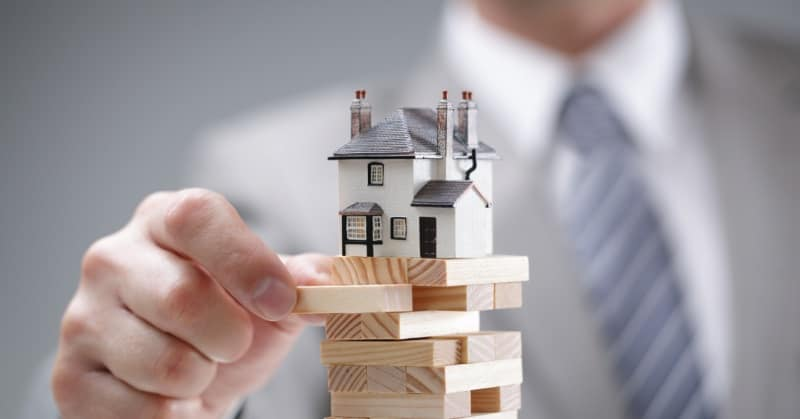 Fixed rates man holding blocks with house