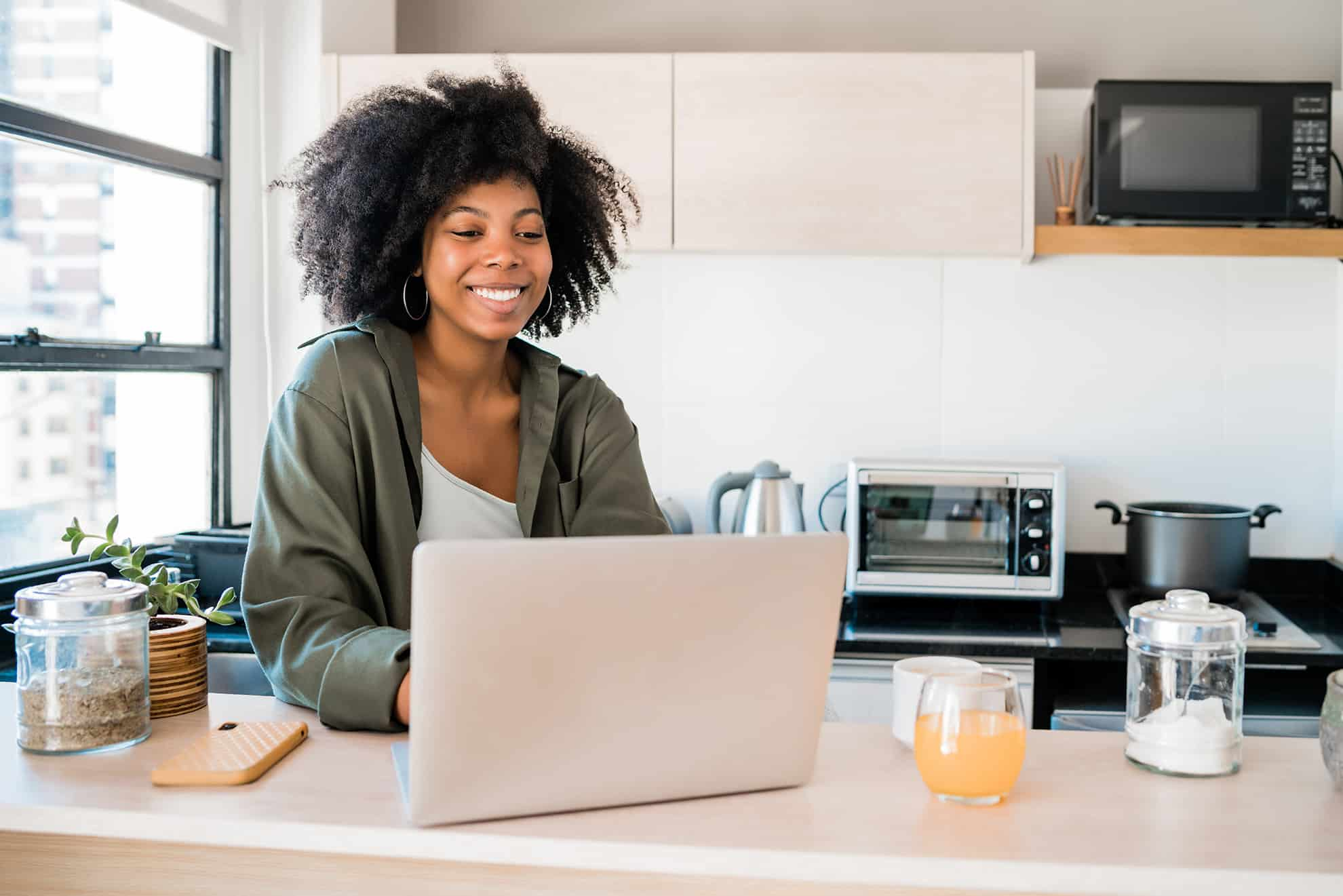 Young woman watching virtual home tour on laptop